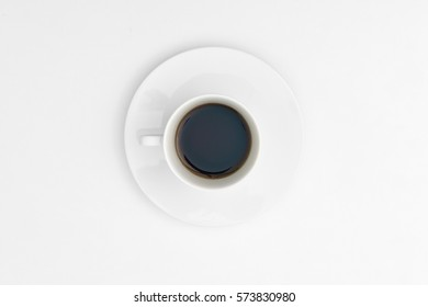 Coffee in ceramic cup on white background. Top view.