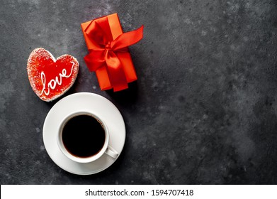 Coffee and cheesecake - heart-shaped cakes with the inscription Love, for Valentine's Day, a gift with a red ribbon on a stone background with copy space for your text