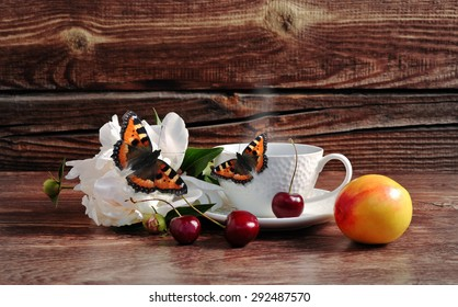 Coffee, cherry, flower and butterfly on a wooden background