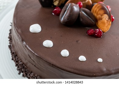 Coffee and chocolate cake decoration glazed and red berries on top