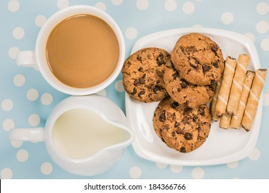 coffee with chocolate cookies and rolls wafer with hazelnut on retro blue with white dots background