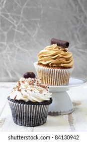 Coffee and chocolate cream and white vanilla cream  cupcakes on a white plate against grunge wooden background, focus on the white cupcake.