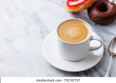 Coffee with chocolate donut in marble table background. Copy space.