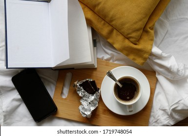 coffee with chocolate while reading a book in the bed. yellow pillows. black modern smartphone. top view. flat lay.