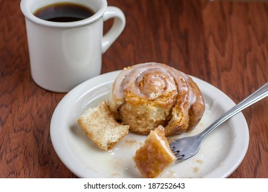 Coffee and a Cinnamon Roll on a wooden table.