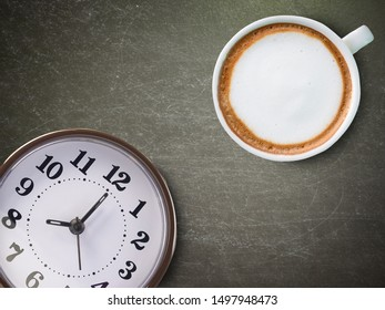 Coffee and clock on the black background. (Morning coffee concept)