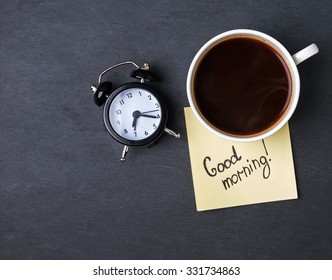 "Coffee, clock and paper with text ""Good morning"" on the black background, top view."