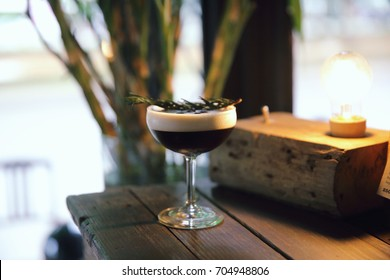 Coffee cocktail with coffee bean and rosemary on top with wood background
