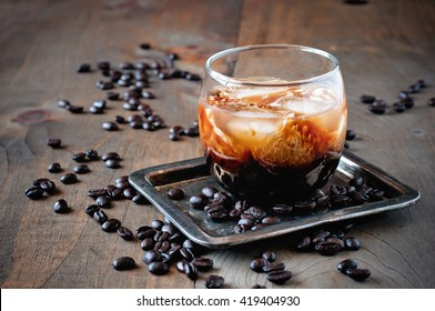 Coffee cocktail with cream, White Russian,  liquor in glasses with coffee beans on a wooden background, selective focus, toned image