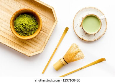 Coffee and cocktails with matcha concept. Matcha latte near bowl with matcha powder and whisk on wooden tray white background top view copy space