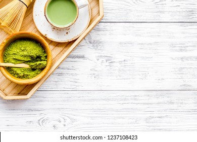 Coffee and cocktails with matcha concept. Matcha latte near bowl with matcha powder and accessories on white wooden background top view space for text