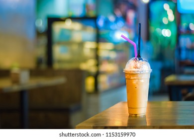 Coffee or cocoa frappe on the wooden table with the blurred background of dessert showcase in the coffee shop