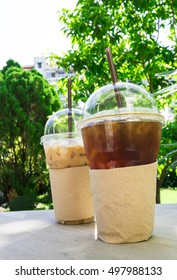 Coffee. Cold coffee.Black coffee and latte coffee in 2 plastic cups on garden background.Cafe in the park in summer time.Coffee for two people in a coffee shop.