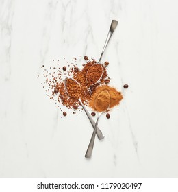 Coffee concept. Flat lay of spoons with ground and instant coffee on marble background. Top view, square crop.