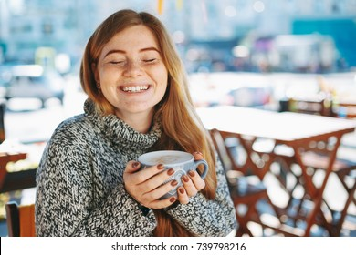Coffee concept. Happy woman holding coffee with hands while keeping eyes closed. Natural reddish girl with freckles, dressed in soft wool sweater, smiling while holding a big cup of coffee latte.