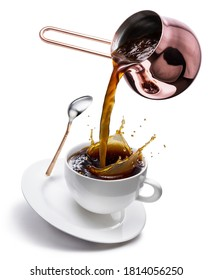 Coffee concept image. Coffee pouring into the cup with splaching from the cooper cezve. Isolated on white background.