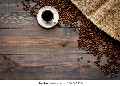 Coffee concept. Roasted beans and cup of espresso on dark wooden background top view copyspace