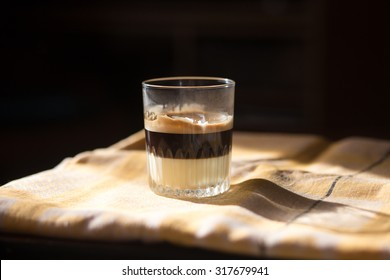 Coffee with condensed milk in a transparent glass. Cafe bombon.