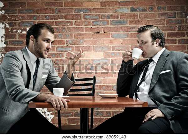 Coffee and conversation between two well dressed men