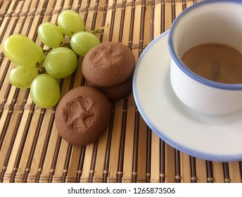 coffee cookies and grapes on brown background