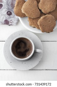 Coffee and cookies on white wooden table, from above