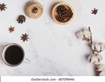Coffee, cotton branch and other small objects on marble background, top view