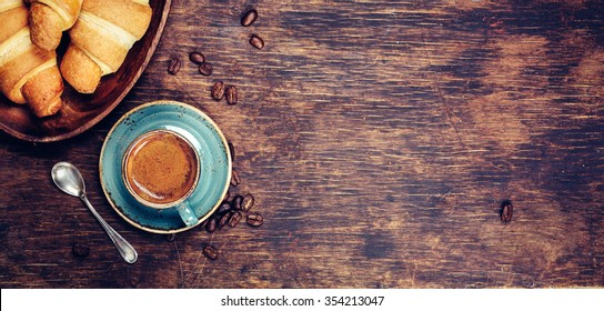 Coffee and croissant with coffee bean. Rustic background with copy space