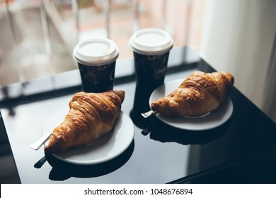 Coffee and croissant for breakfast. Cafe culture. Croissants with two small cups of take away coffee on the black glass table. Office workplace.