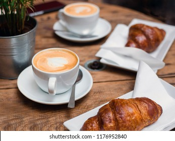 Coffee and croissant for breakfast. Cafe culture. Croissants with two small cups cappuccino with picture, top view