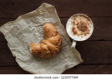 Coffee and croissant for breakfast on rustic wooden table, top view.