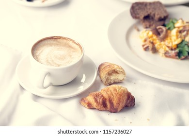 Coffee and croissant for breakfast with shallow depth of field.