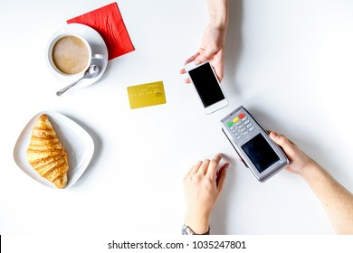 Coffee, croissant and card payment on white background top view