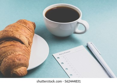 Coffee, croissant and diary planner on a green background. Breakfast concept