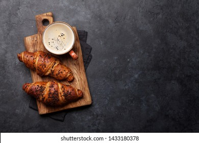 Coffee and croissant on stone table. French breakfast. Top view flat lay with copy space for your text