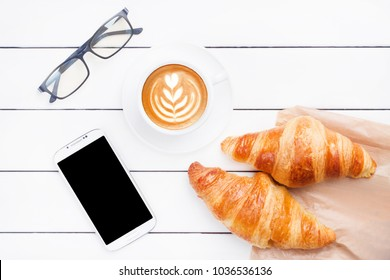 Coffee croissant phone top view breakfast morning work office