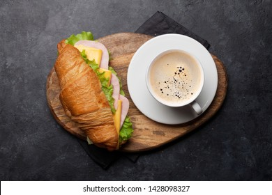 Coffee and croissant sandwich on stone table. French breakfast. Top view flat lay