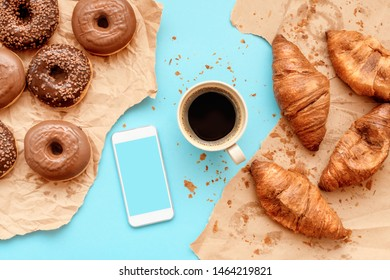 Coffee croissants and chocolate doughnuts for breakfast with smart phone mock up, top view of sweet snack on table