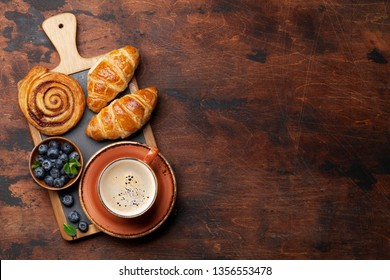 Coffee, croissants, cinnamon rolls and berries breakfast. On wooden table. With notepad for your text