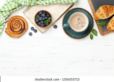 Coffee, croissants, cinnamon rolls and berries breakfast. On wooden table. Top view with copy space for your text