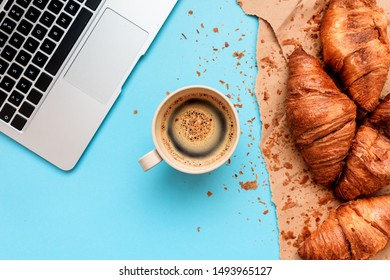Coffee and croissants for messy breakfast in business office, top view flat lay