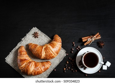 coffee and croissants on black background