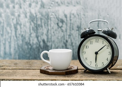 Coffee cup with alarm clock on a rainy day window background