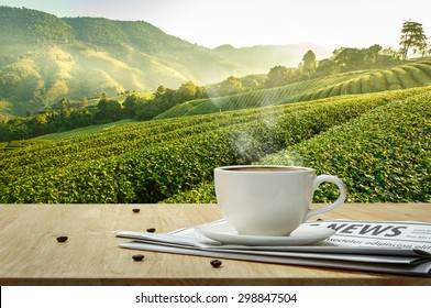 Coffee cup and Coffee bean roating with newspaper on the wooden table and the Plantations background