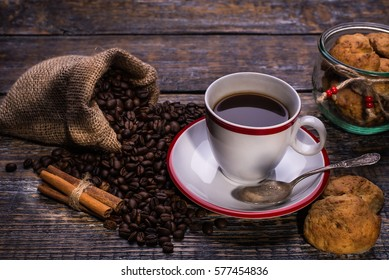 Coffee cup, coffee beans and biscuits, cookies  on wooden background