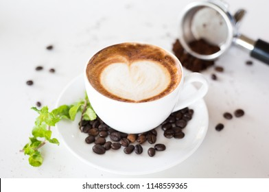 Coffee cup with coffee beans in cafe