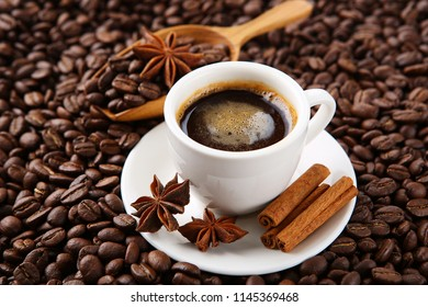 Coffee cup with coffee beans with cinnamon, pumpkins and star anise.