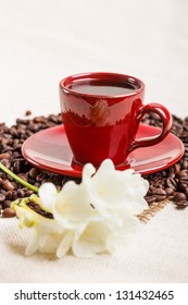 Coffee cup with coffee beans and freesia flower