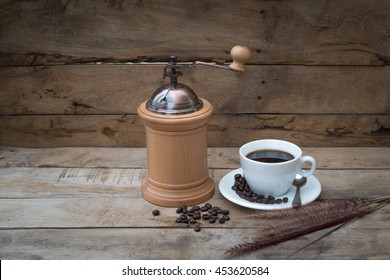 Coffee cup with coffee beans ,Coffee grinder and the grass on vintage old wooden board