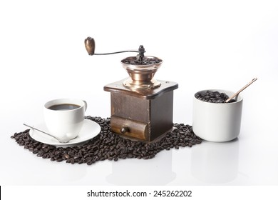 A coffee cup and coffee beans and grinder isolated white at the studio.