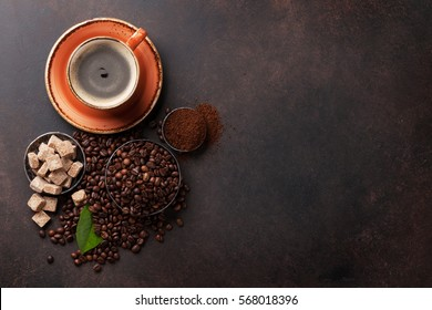 Coffee cup, beans and ground powder on stone background. Top view with copy space for your text